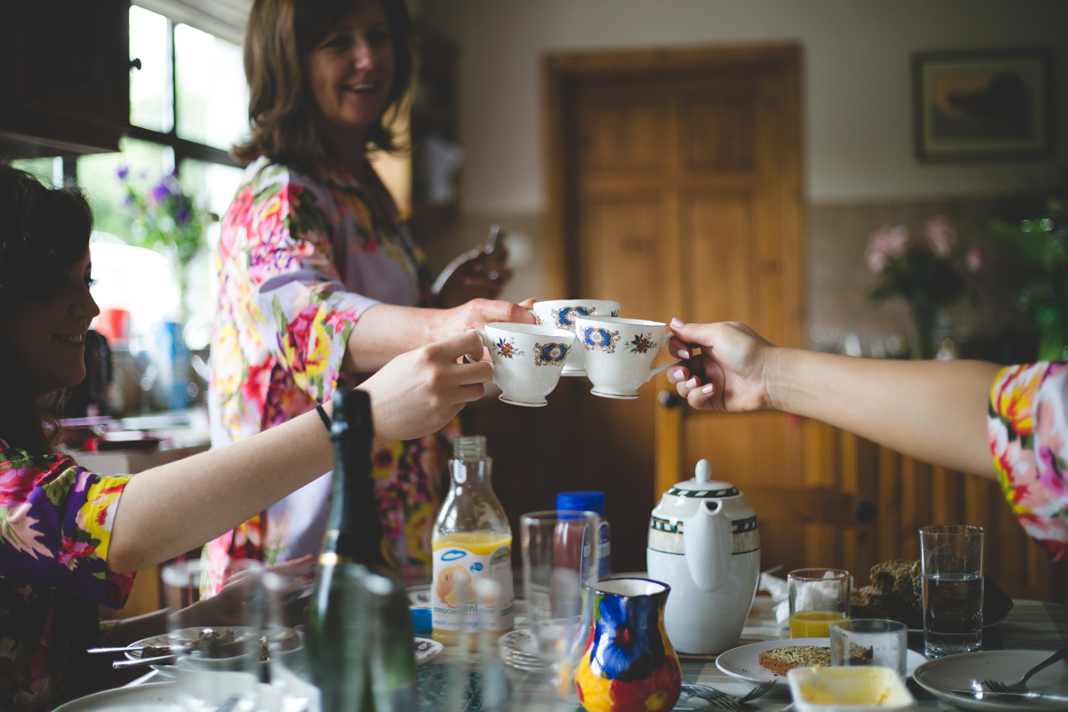 Family clink together cups of tea on the wedding morning