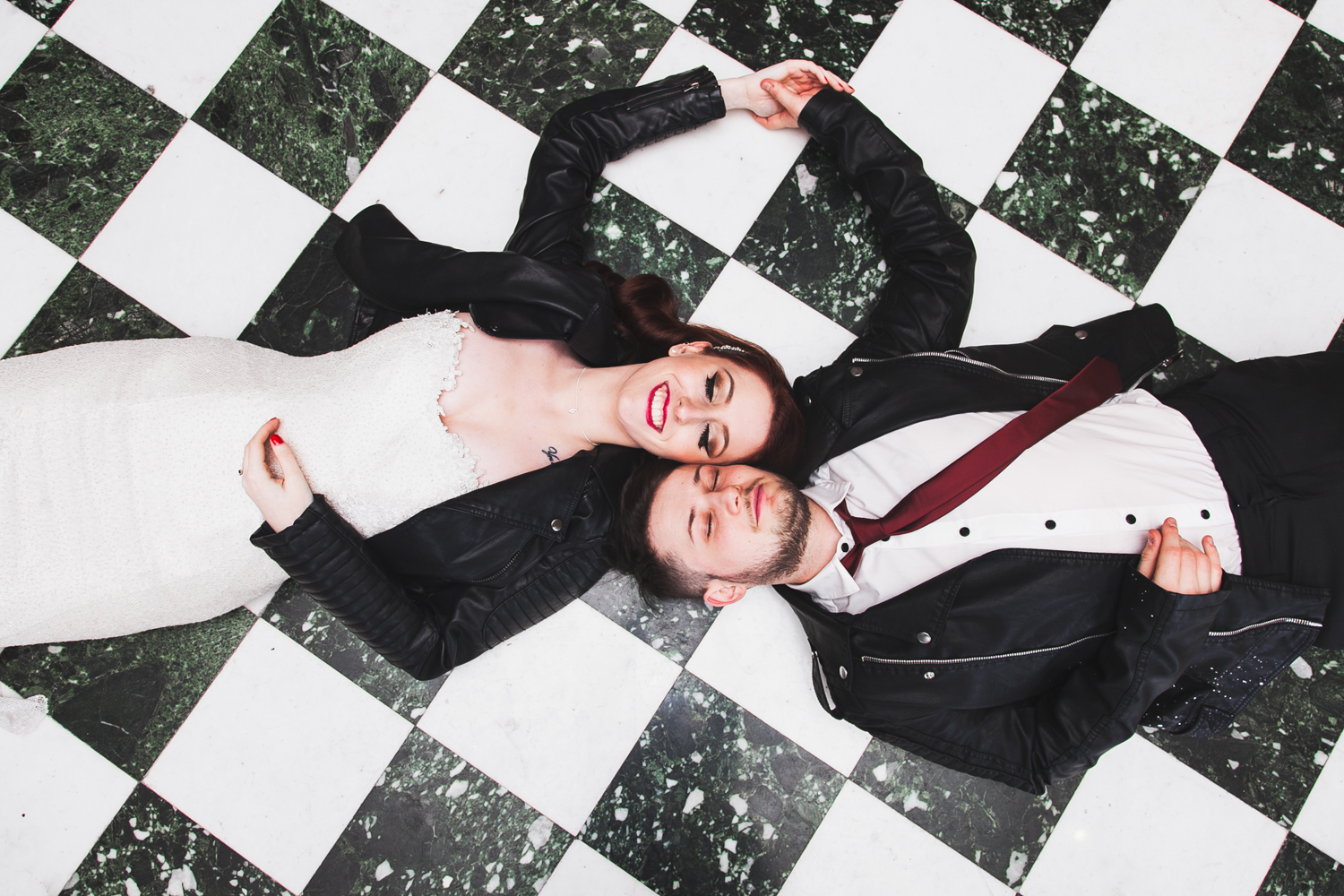 Overhead shot of newlywed couple lying side by side on the floor