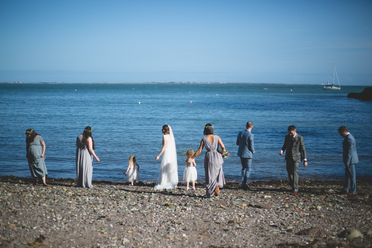 Bridal party skim stones at Gorey beach during wedding shoot