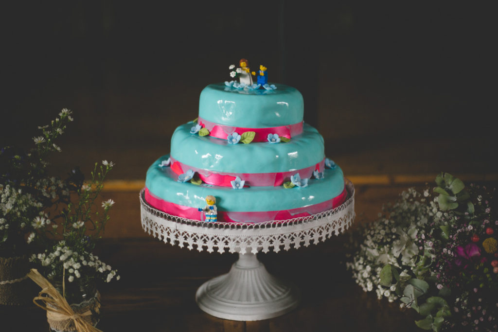 Homemade Blue wedding cake with lego toppers and pink ribbon