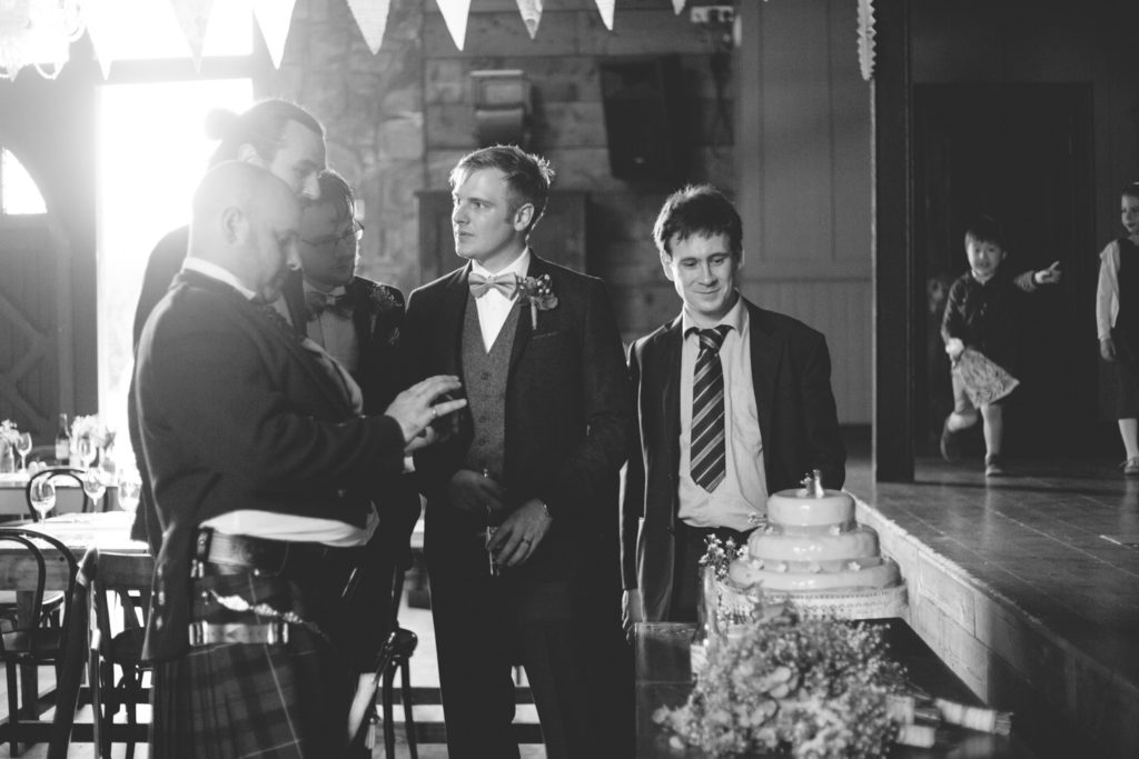 black and white shot of guys admiring the homemade wedding cake