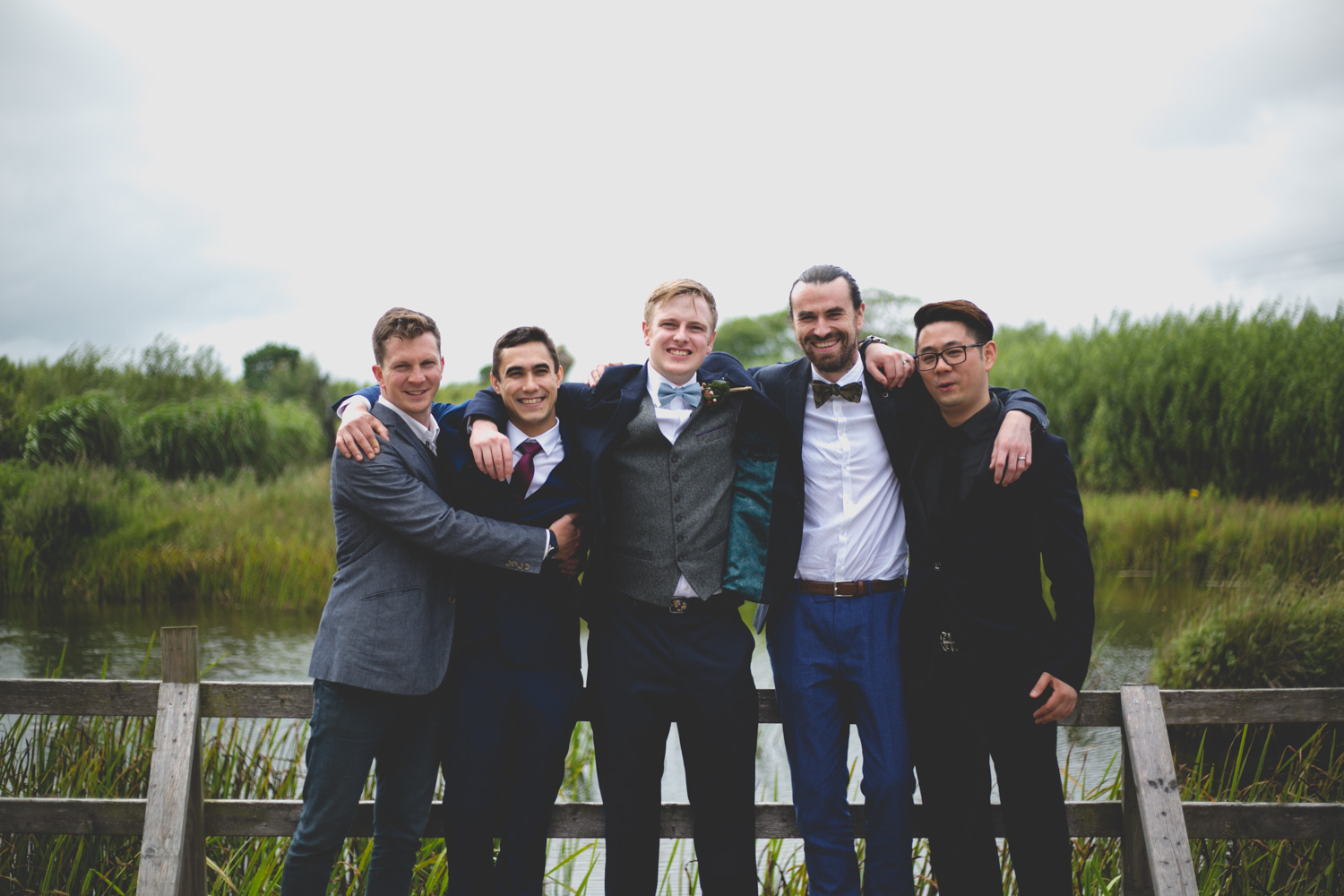Groom and groomsmen hugging at lakeside wedding