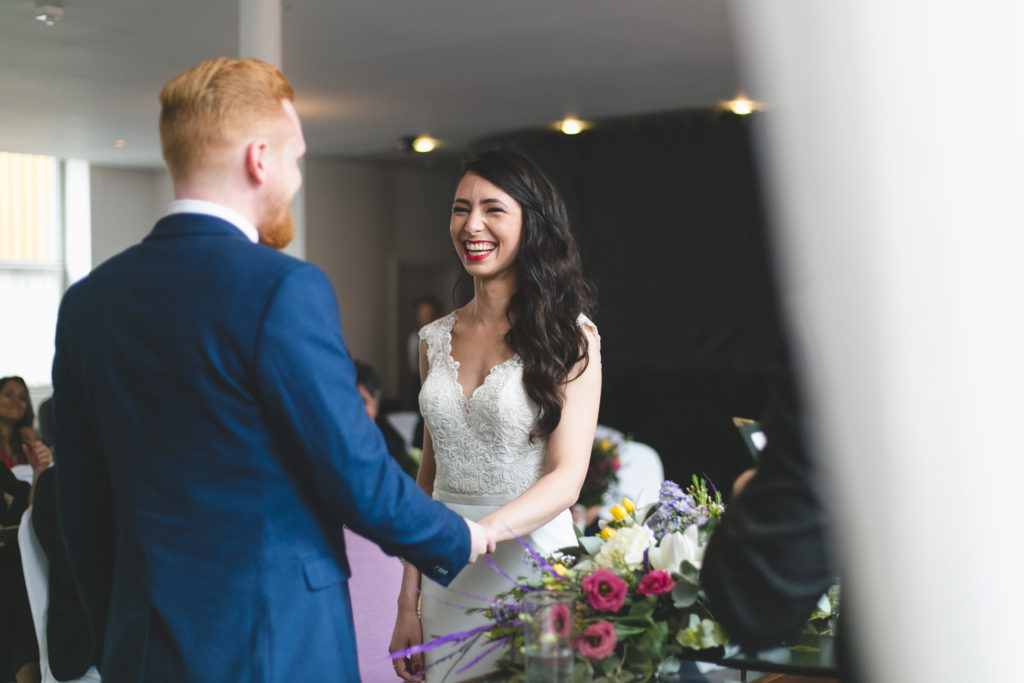 Couple laughing while exchanging wedding vows