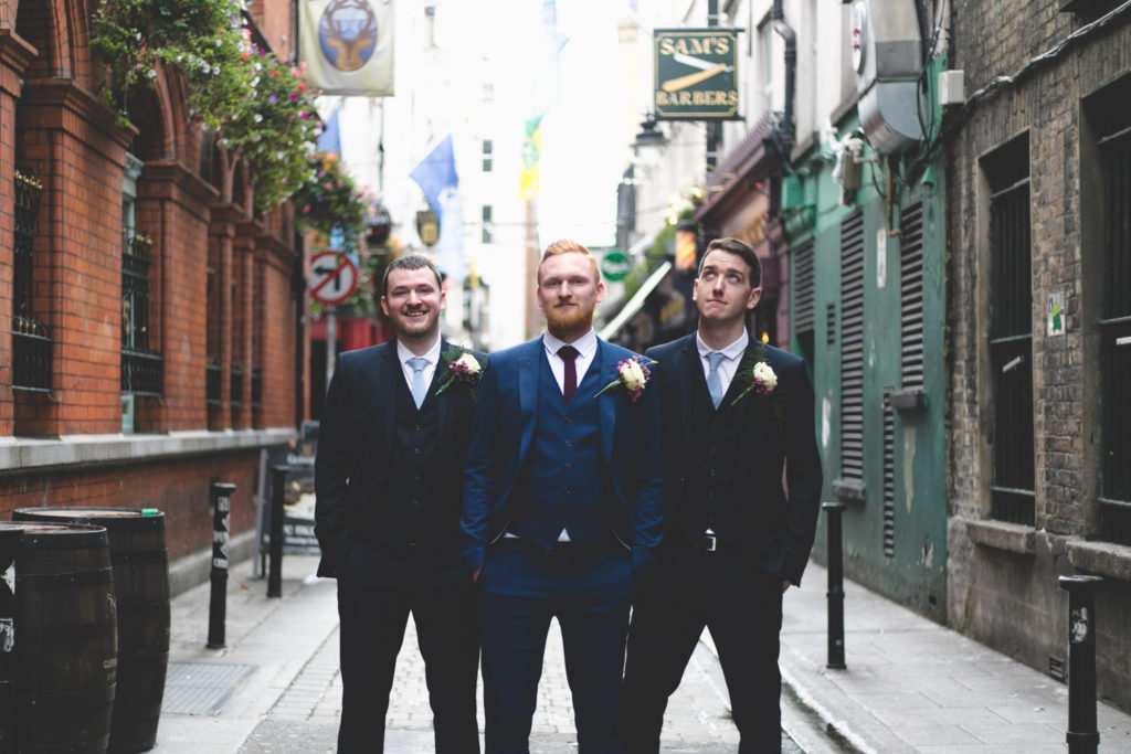 groom and groomsmen pose on dame lane