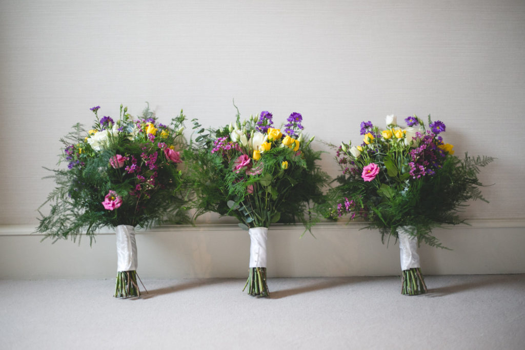 photograph of three green, yellow, pink and purple wedding bouquets
