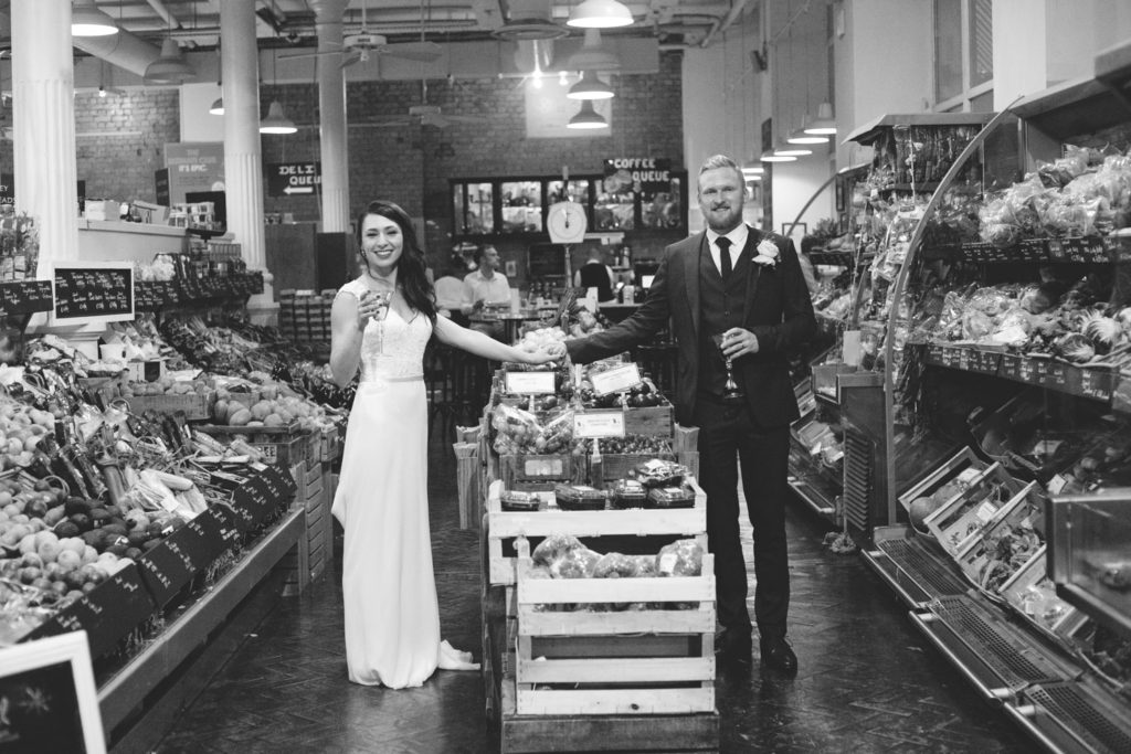 Groom and bride pose in supermarket at Wedding at Fallon and Byrne