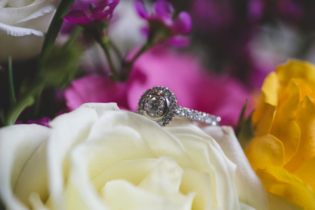 Circular diamond covered ring on bouquet of roses