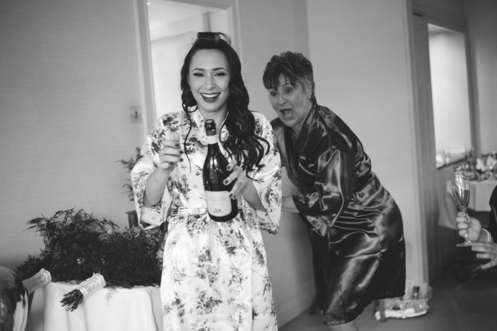 black & white shot of bride and mother popping champagne bottle