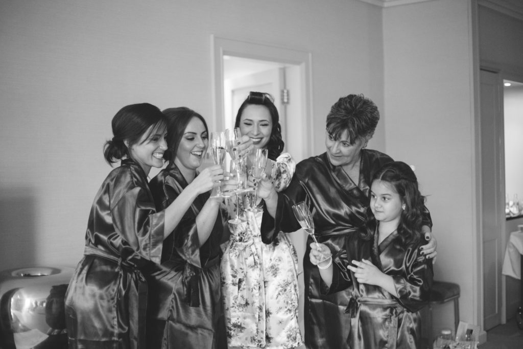 cheers! bride and bridesmaids clinking champagne glasses