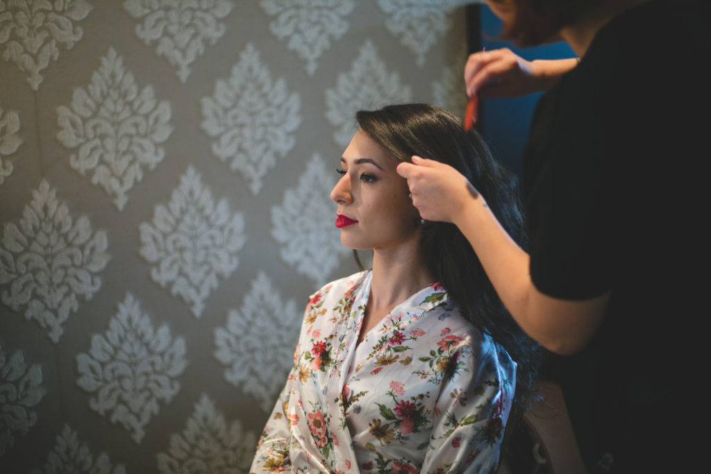 Bride getting hair styled in floral dressing gown