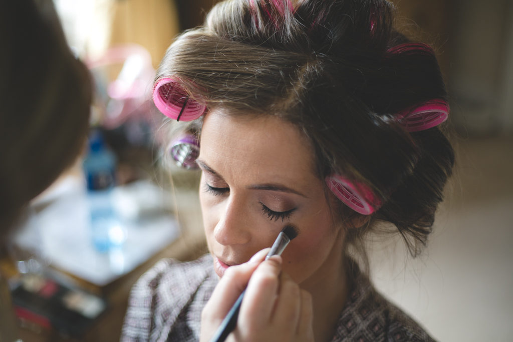 Bride in curlers getting make-up applied