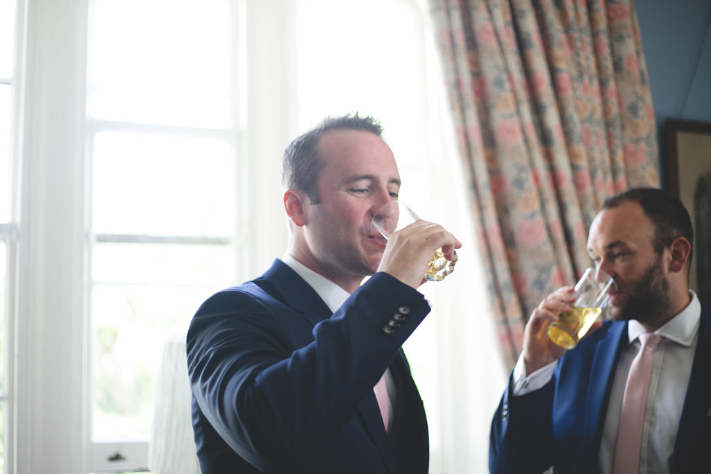 Groom having a drink of whiskey