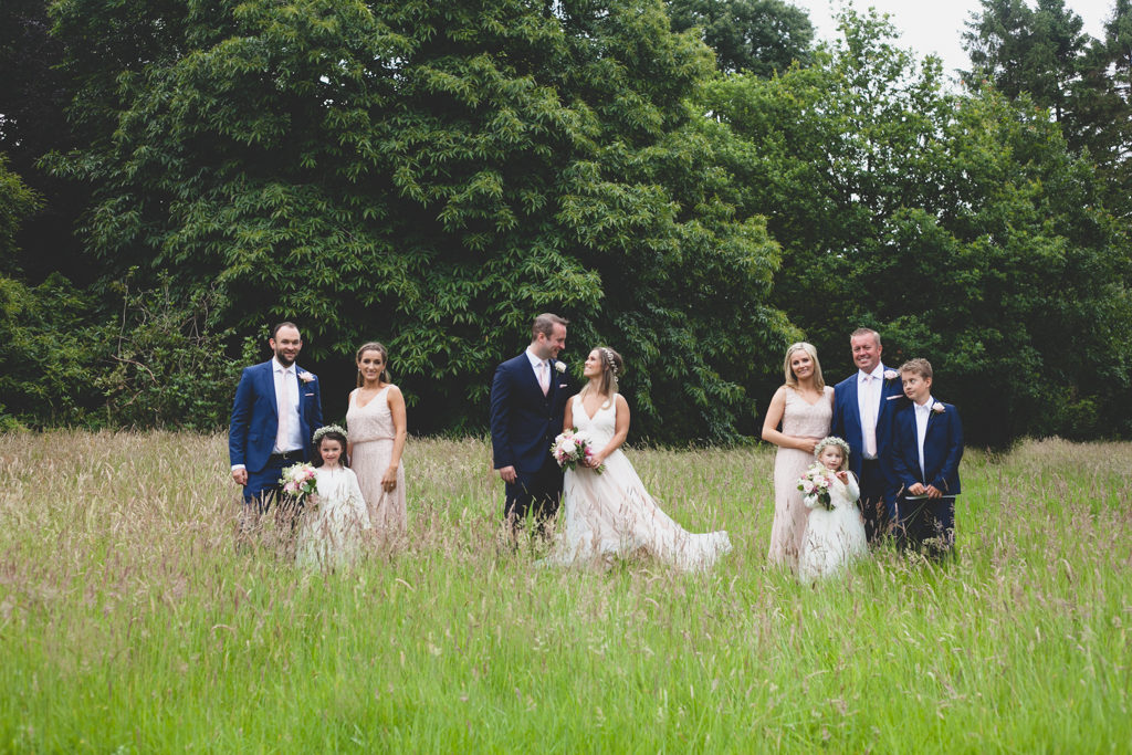 wedding party portraits taken in a field with high grass