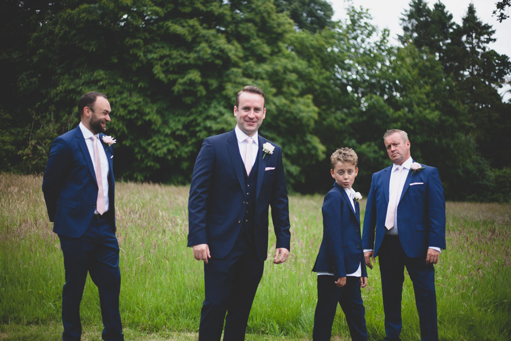 Groom and pageboy posing in a green field
