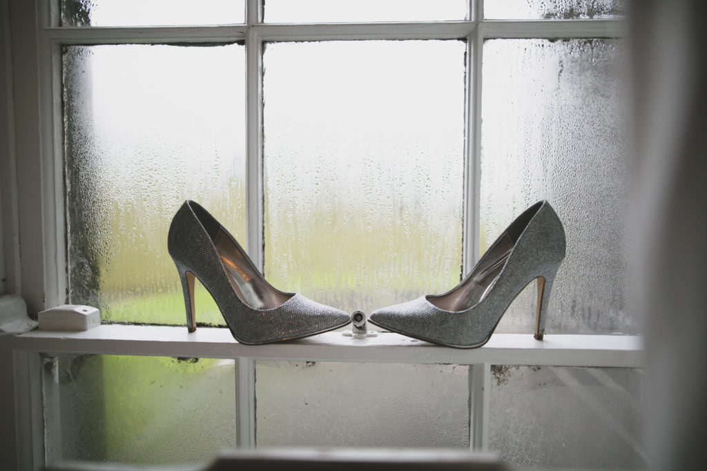 Sparkly silver wedding high-heels placed on a window ledge