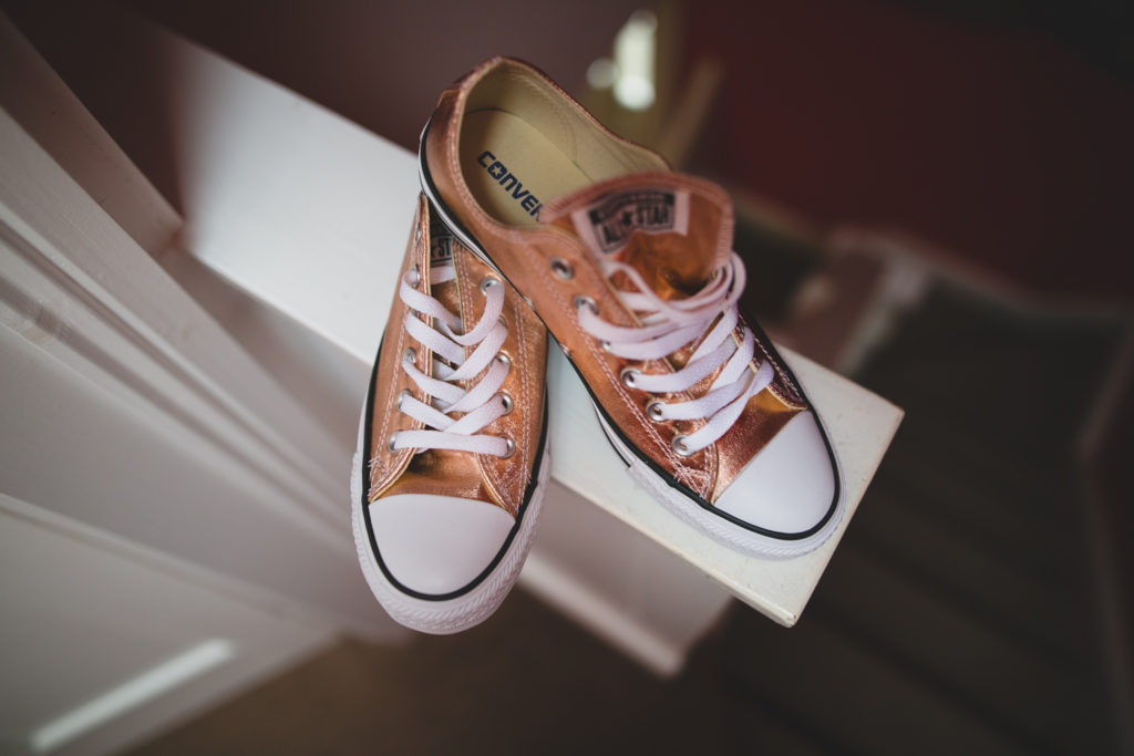 A pair of shiny rose-gold copper converse