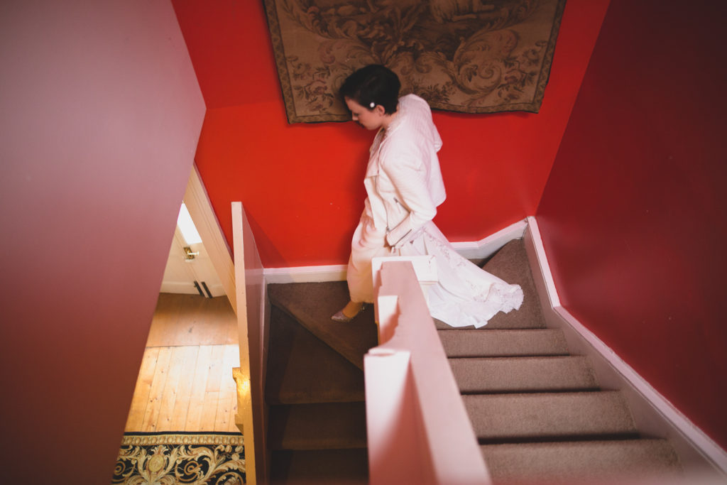Bride descends stairs past vivid red wall
