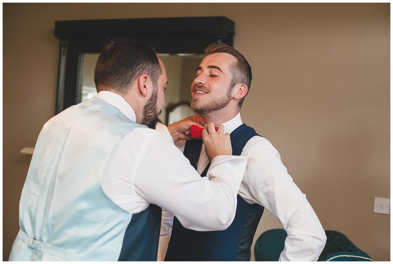 Groomsman adjusts the bowtie on the groom