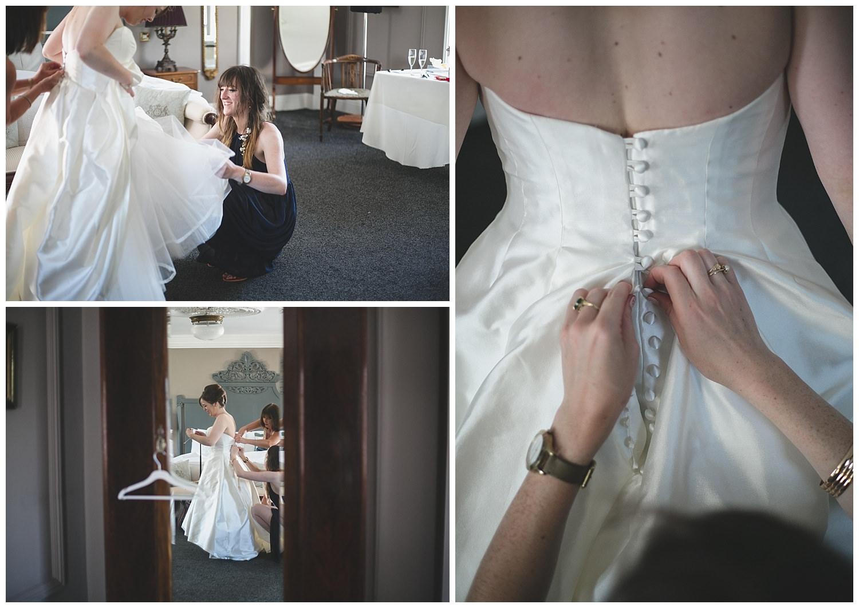 Close-up of hands doing up wedding dress buttons