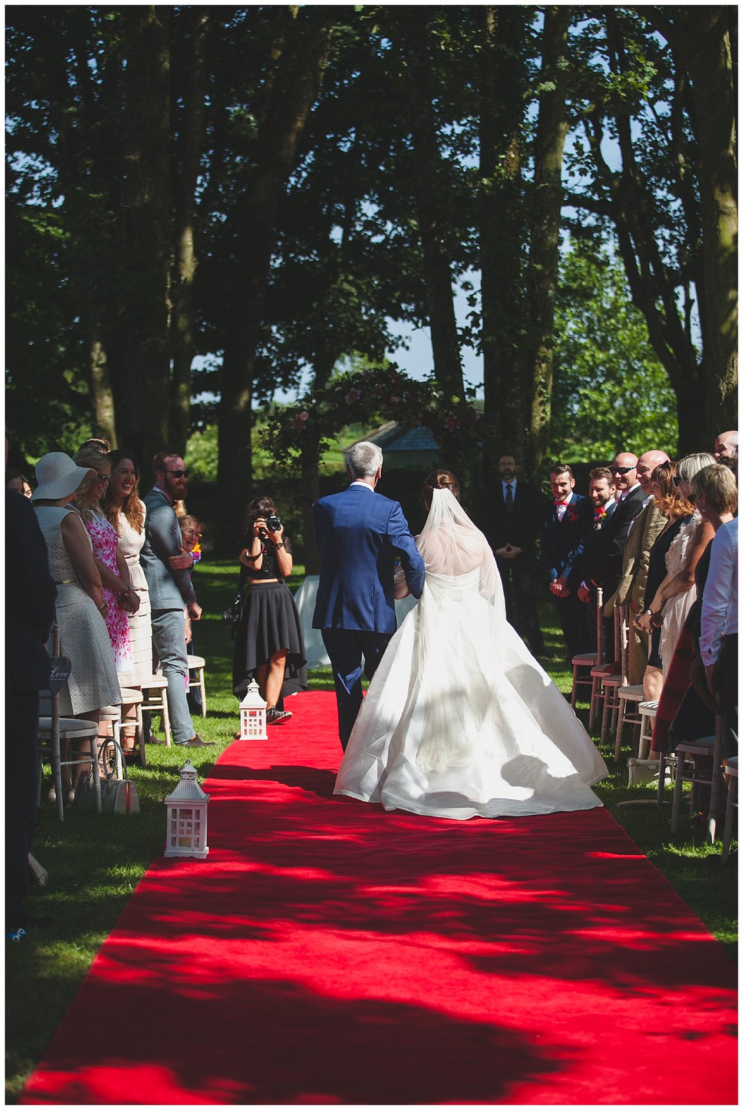 The back of the brides dress as she walks down the aisle