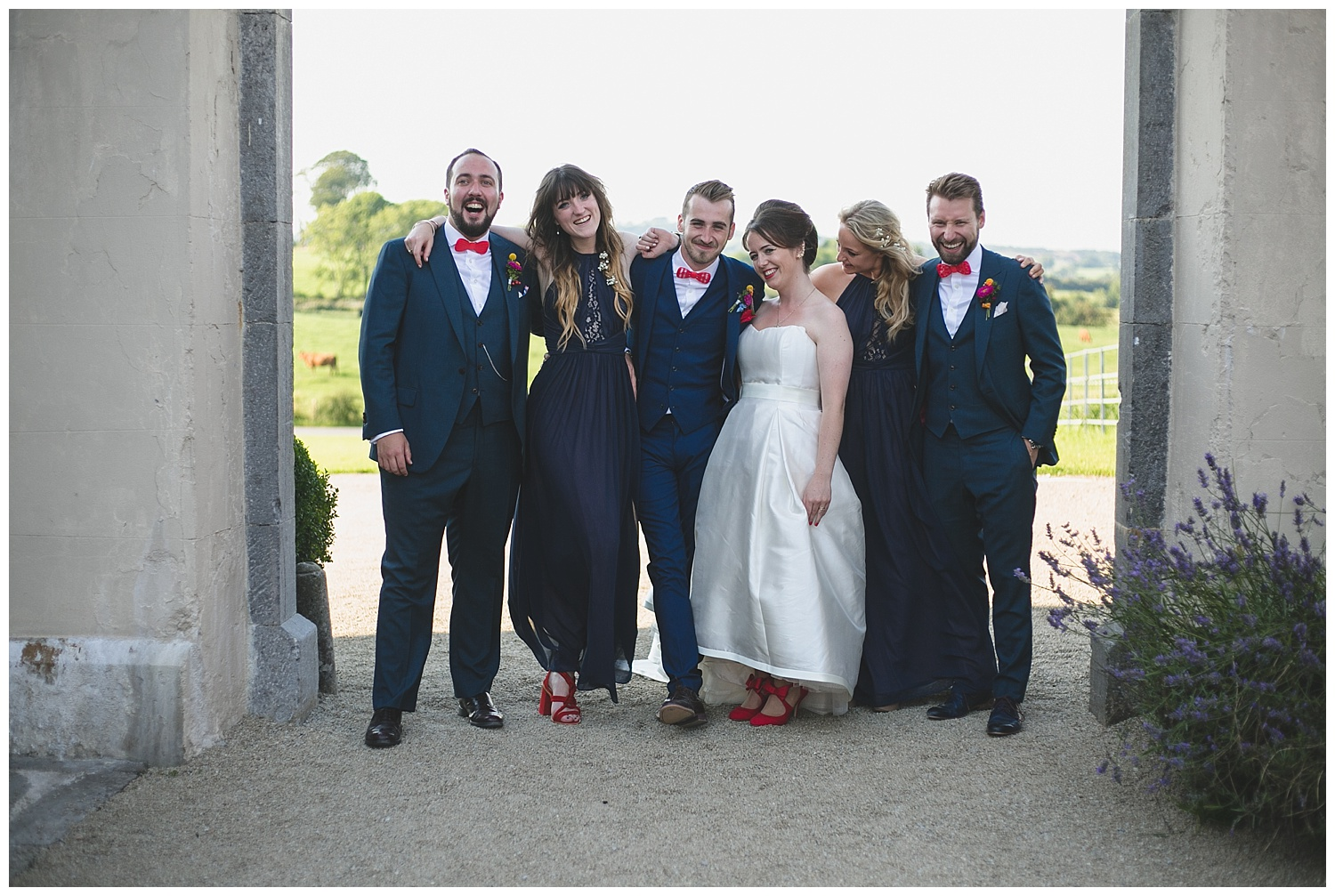 Bridal party portrait under archway at Clonabreany House