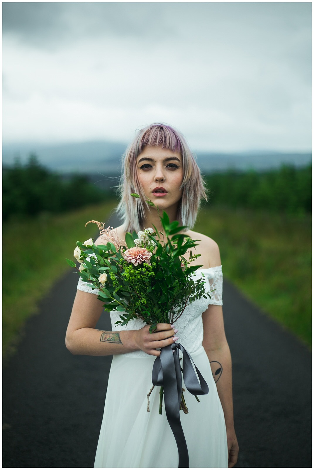 Alternative styled bride holding a wild bouquet - Wild Things Wed Photography
