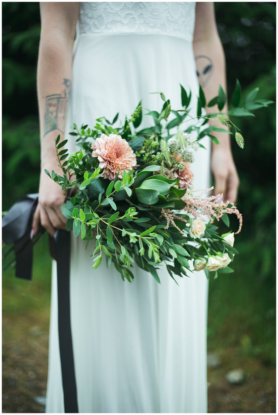 Wild Green and pastel orangey pink flowers in a wedding bouquet tied with grey ribbon
