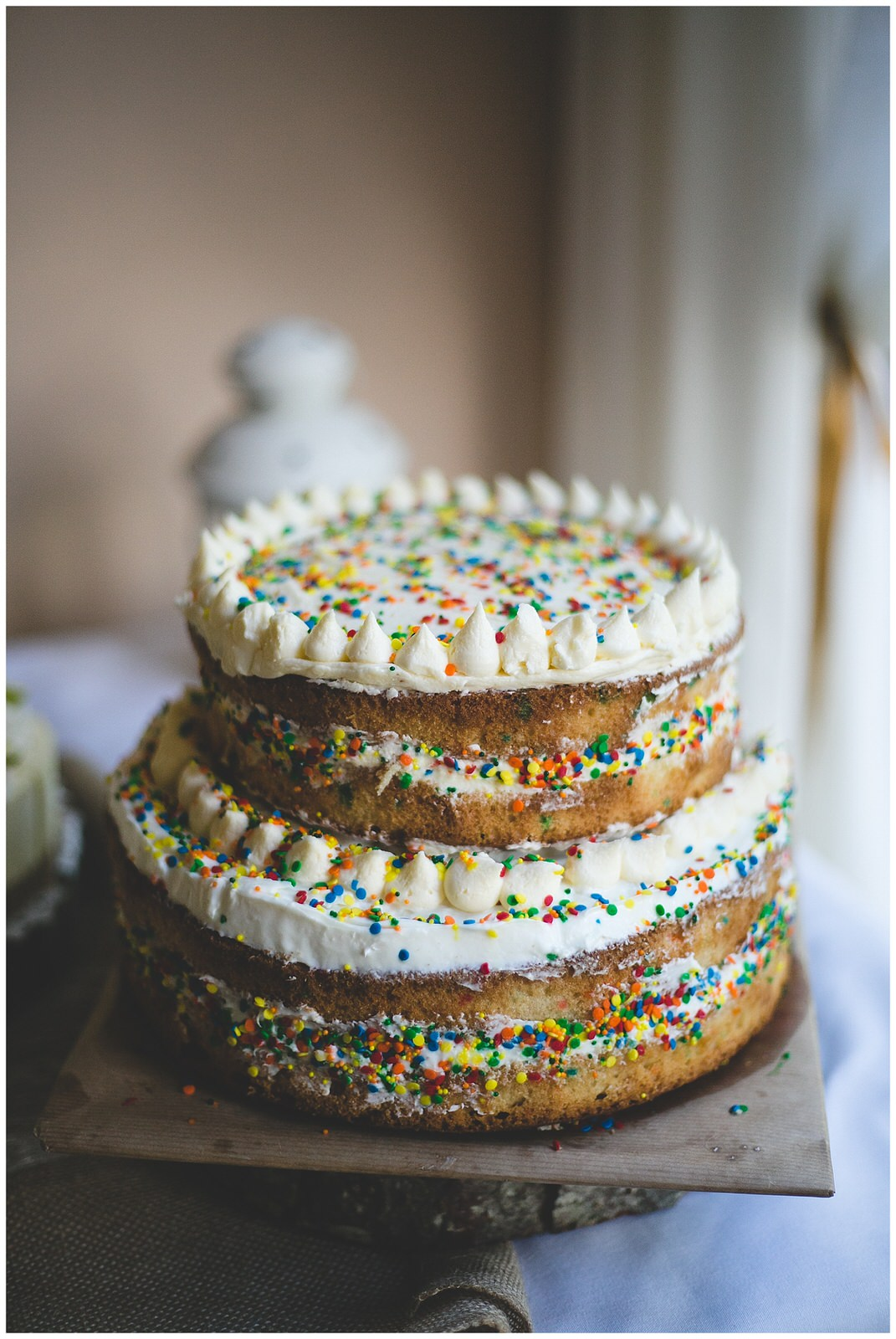 Natural raw buttercream iced cake decorated with sprinkles
