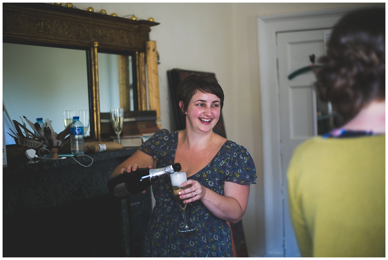 Bridesmaid laughs as she pours champagne