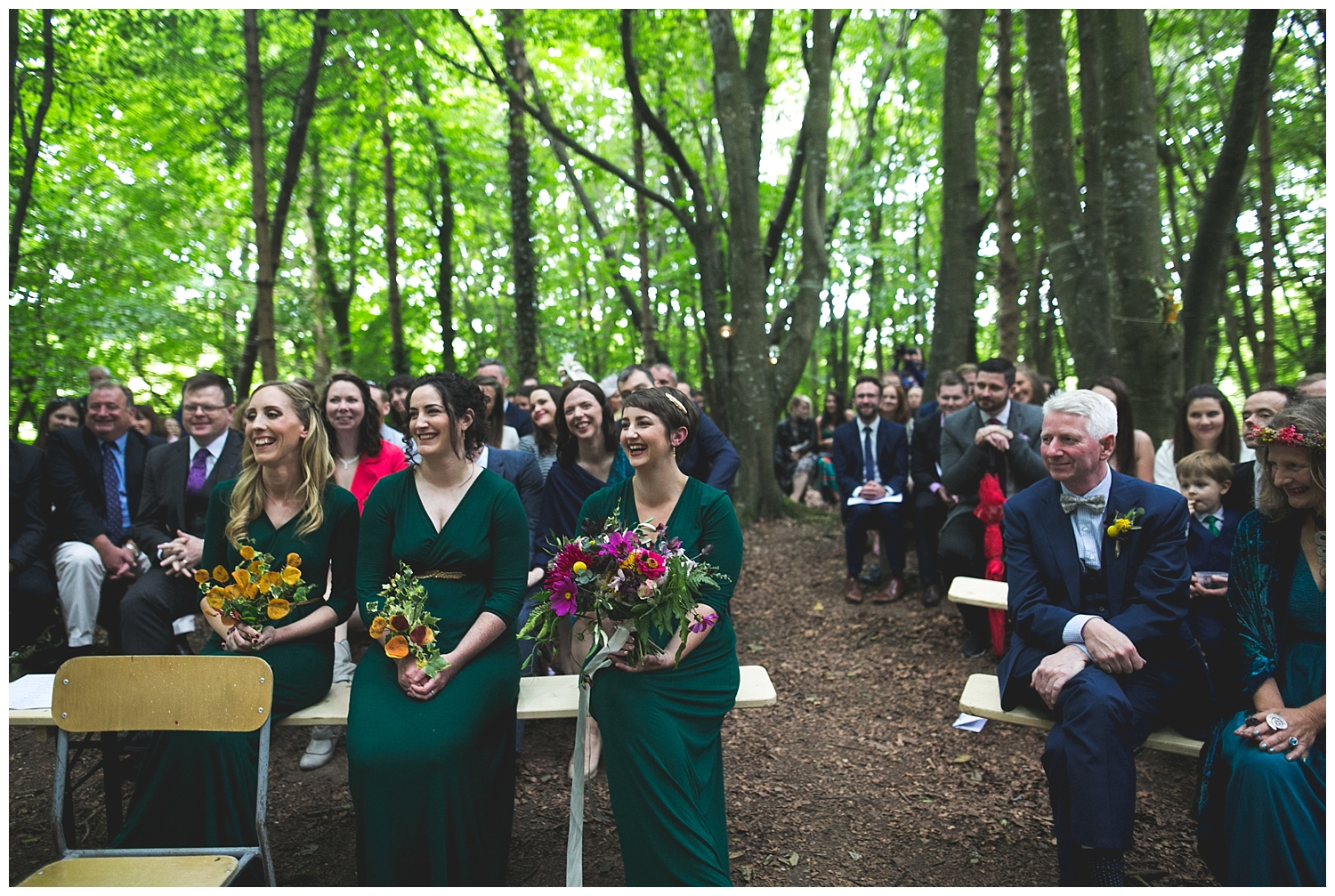 Guests smiling and laughing at an outdoor wood ceremony