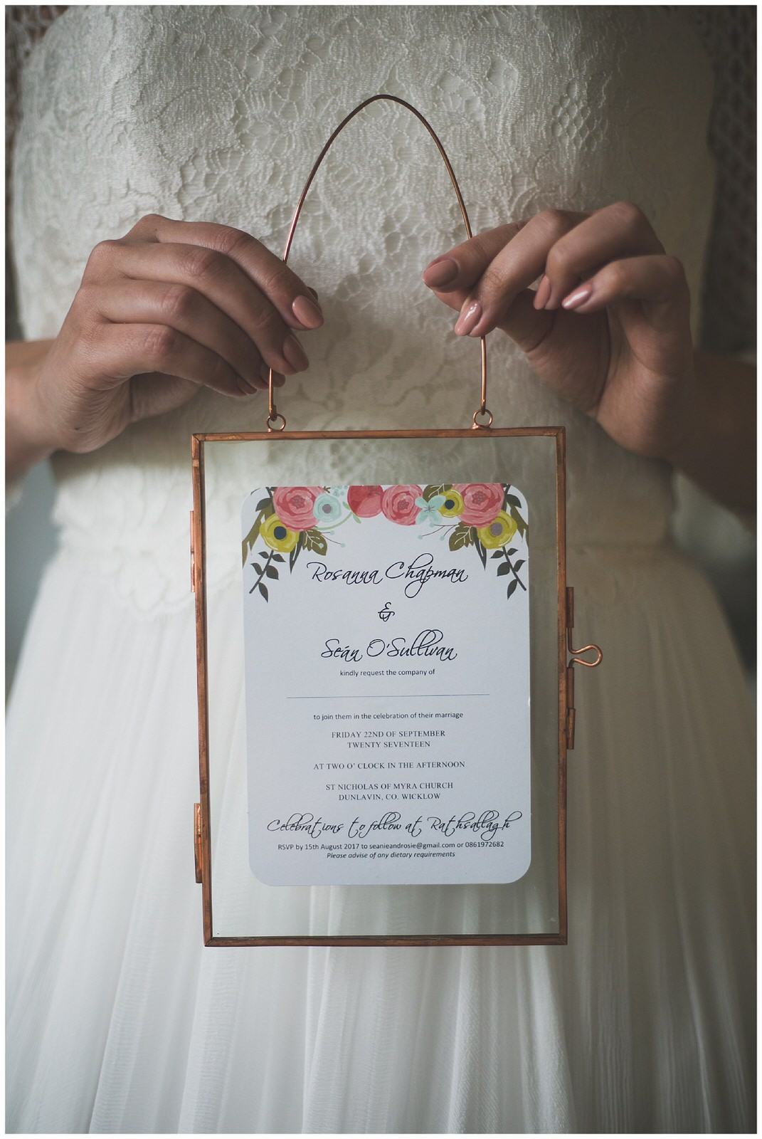Rose gold metal glass frame with wedding invitation