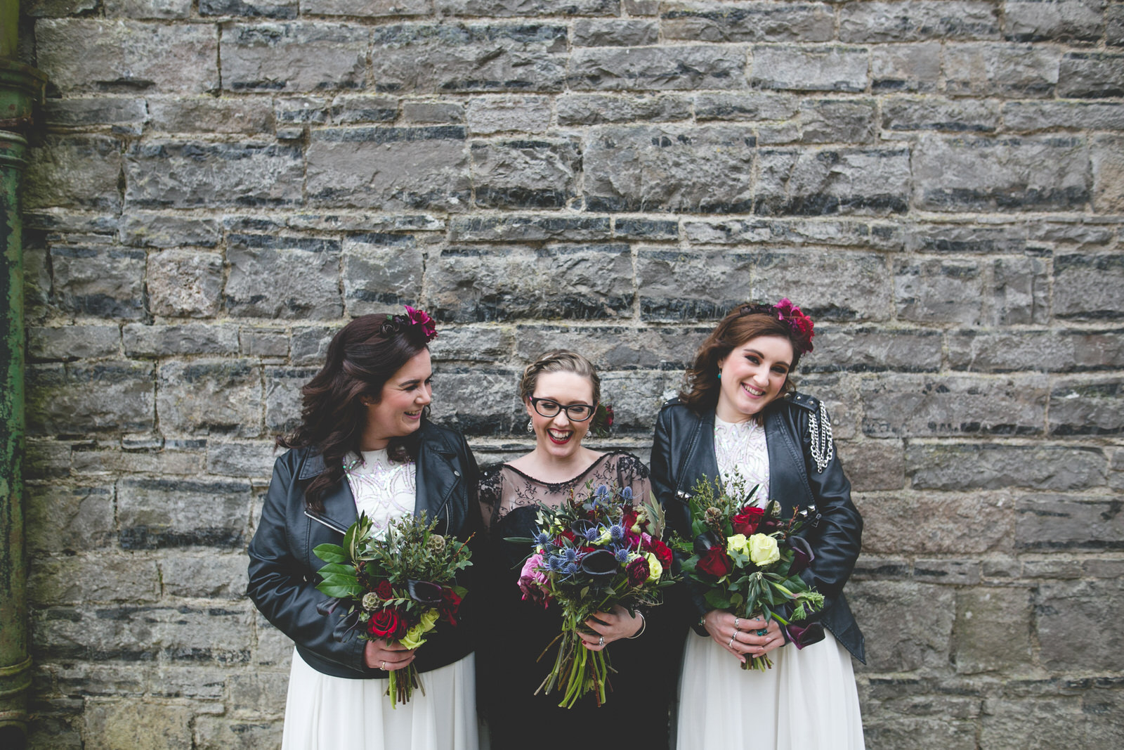 Bride wearing a black wedding dress with Bridesmaids in white and leather jackets