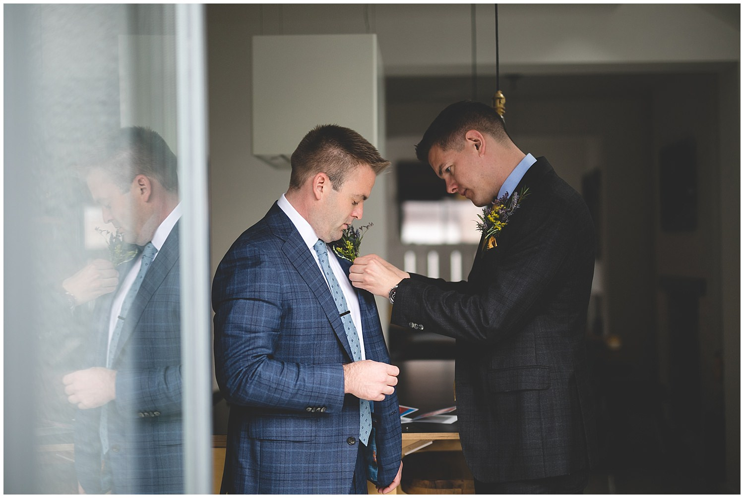 Grooms fixing each others boutonnieres