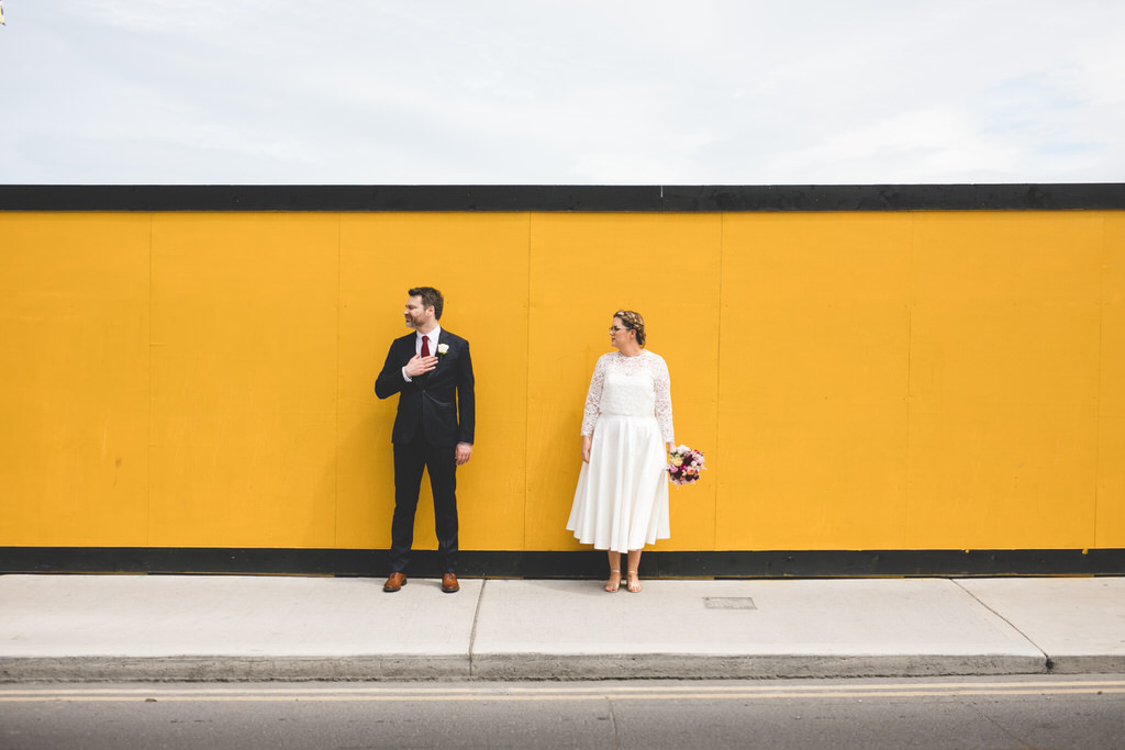 Funky colourful wedding photo in front of bright yellow hoarding