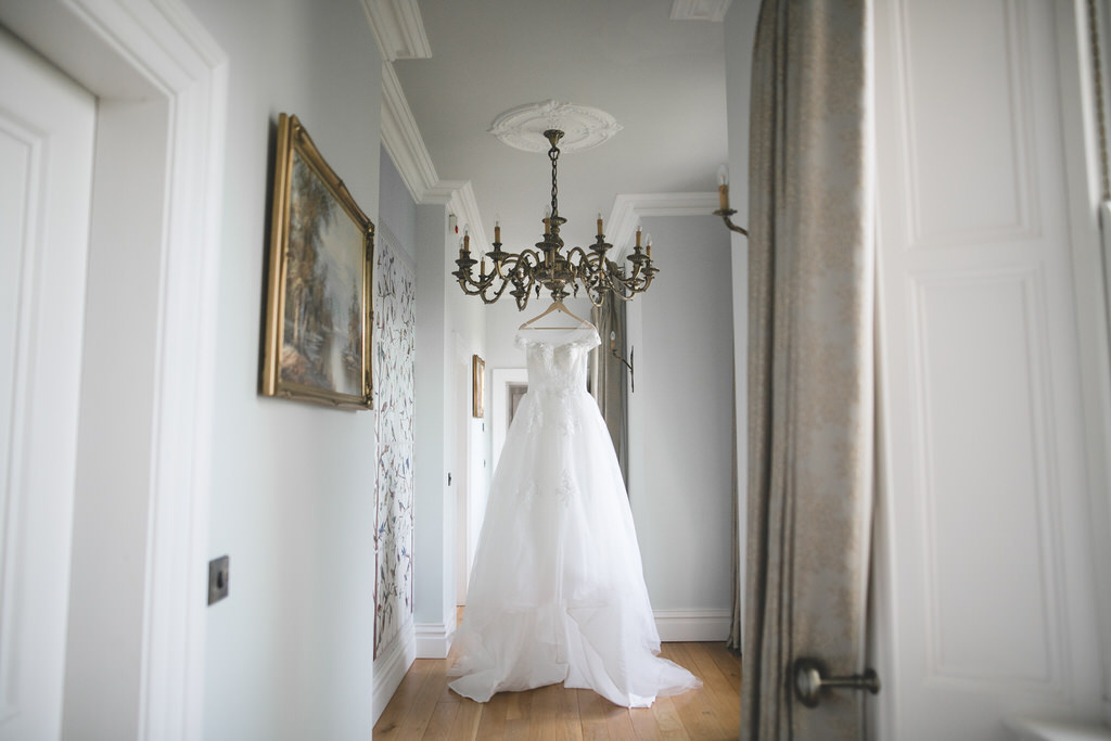 detail shot of a tulle wedding dress hanging from a chandelier