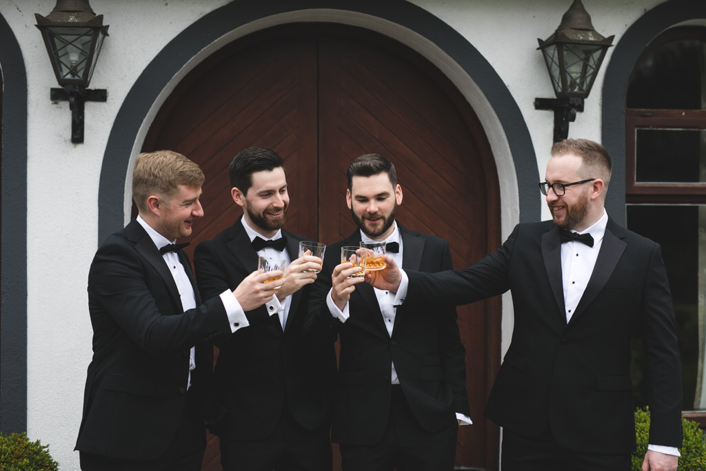 Groom & groomsmen toasting with whiskey on the wedding morning