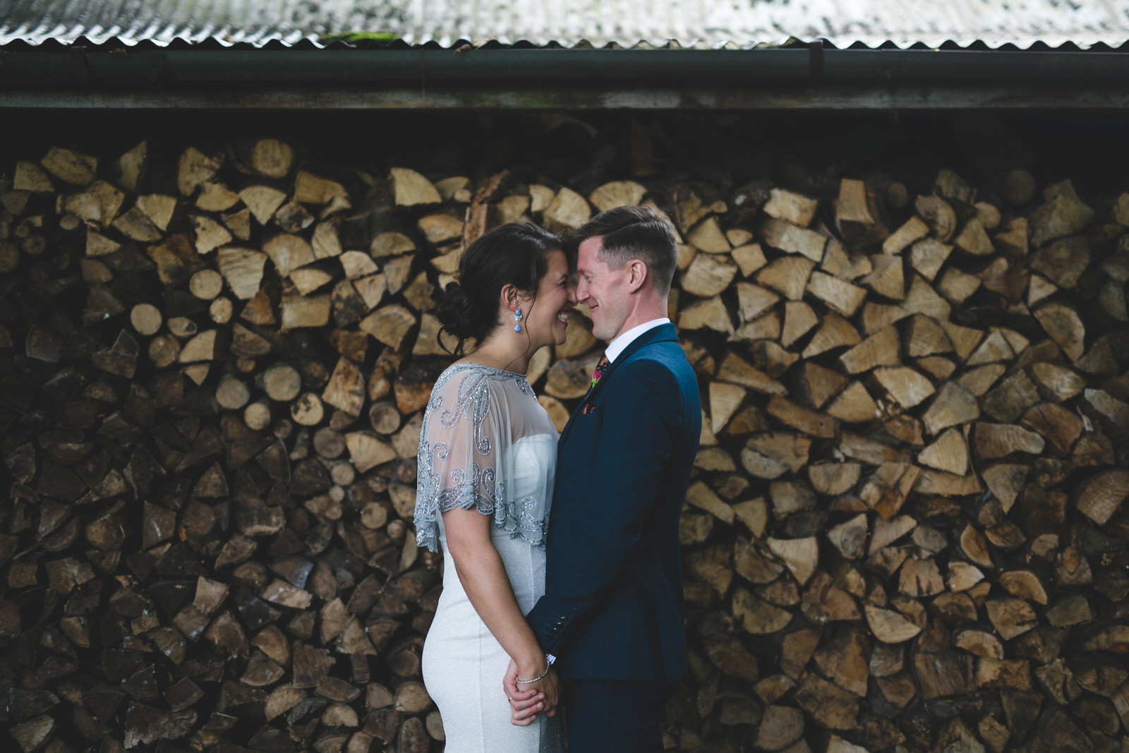 cute wedding portraits in front of a wall of cut wood
