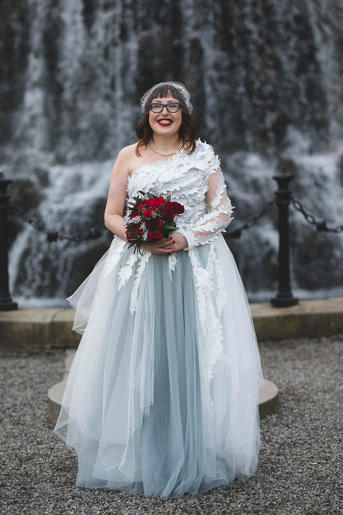 alternative gray white and blue toned wedding dress with cutout leaf shapes and a birdcage veil